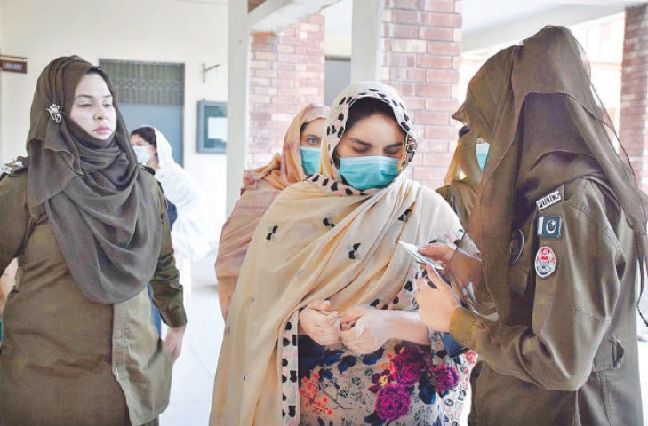 A policewoman checking the identity card of a voter at a polling station during the by-election in Daska constituency on Saturday.—APP