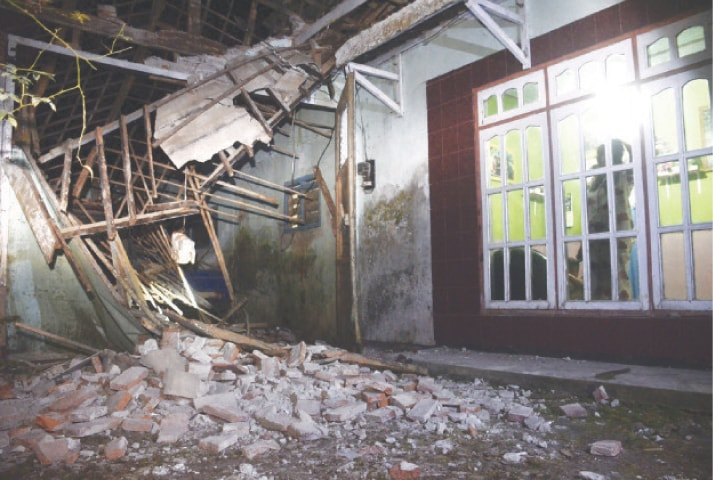 MALANG: A woman surveys a part of her house damaged by an earthquake in East Java on Saturday.—AP