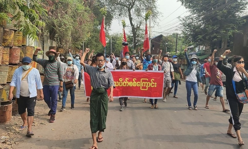 This photo taken and received from an anonymous source via Facebook on April 10, 2021, shows protesters holding a banner as they march during a demonstration against the military coup in Mandalay. — AFP/Anonymous source
