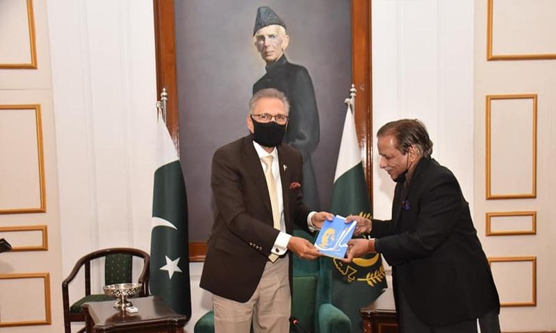 لکھاری صدر عارف علوی کو کتاب پیش کرتے ہوئے— کے ای سی فیس بک پیج