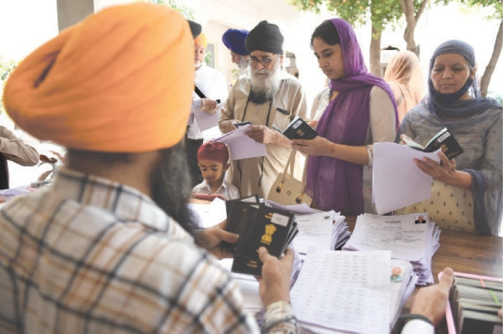 AMRITSAR: Sikh pilgrims collect their passports from the Shiromani Gurdwara Parbandhak Committee at the Golden Temple complex on Sunday before leaving for Pakistan to celebrate the Vaisakhi festival.—AFP