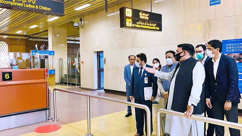 KARACHI: Interior Minister Sheikh Rashid Ahmed asking staff at the airport to increase immigration counters at the terminal to facilitate travellers.—APP