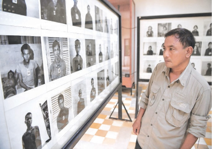 A Sept 2, 2020, file photo shows Norng Chan Phal, who survived internment in a prison during Khmer Rouge rule, looking at portraits of genocide victims.—AFP