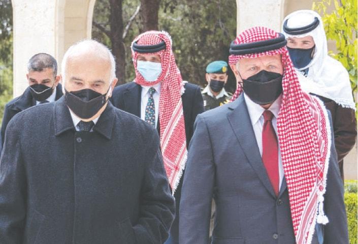 Jordanian King Abdullah II (right), Prince Hassan bin Talal (left) and Prince Hamzah (centre) arrive at the Raghadan Palace on Sunday.—AFP