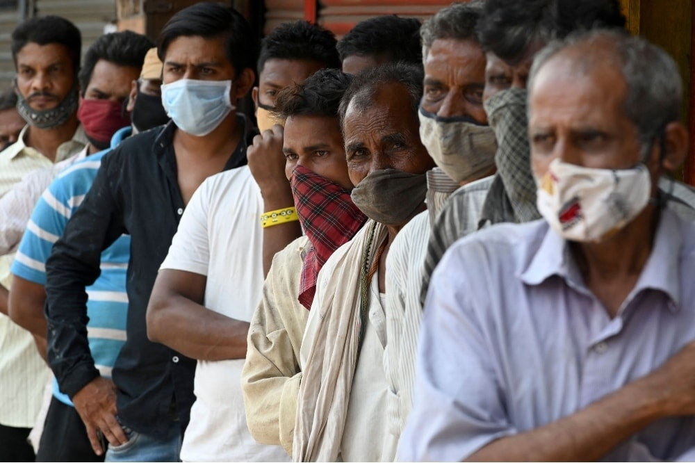People stand in a queue as they wait for food to be distributed by social workers during weekend lockdown restrictions imposed by the state government amidst rising Covid-19 coronavirus cases, in Mumbai on April 11. — AFP