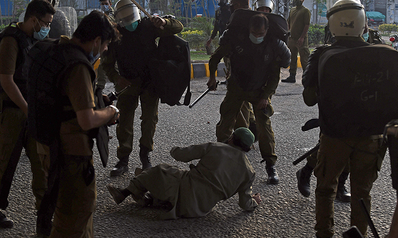 پولیس نے لاہور میں مظاہرے میں شریک ایک شخص کو گھیرے میں لیا ہوا ہے— فوٹو: ا ے ایف پی