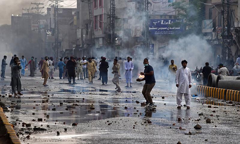 لاہور میں مظاہرین پولیس پر پتھراؤ کررہے ہیں— فوٹو: اے ایف پی