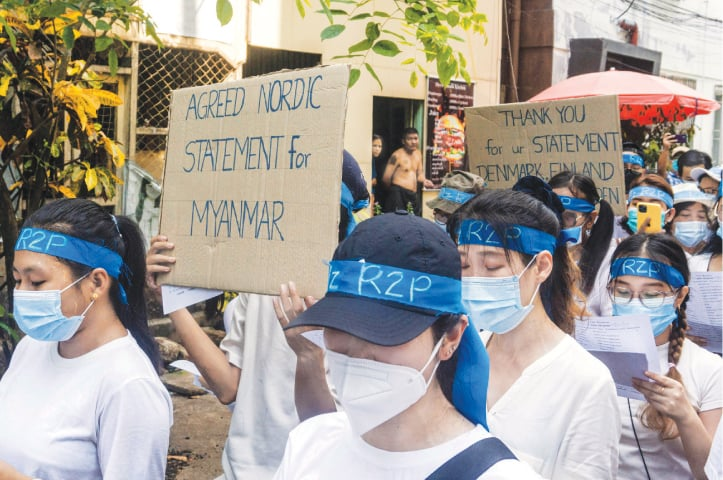 YANGON: Protesters wearing headbands relating to 'R2P', or the 'Responsibility to Protect', take part in a demonstration against the coup on Monday.—AFP