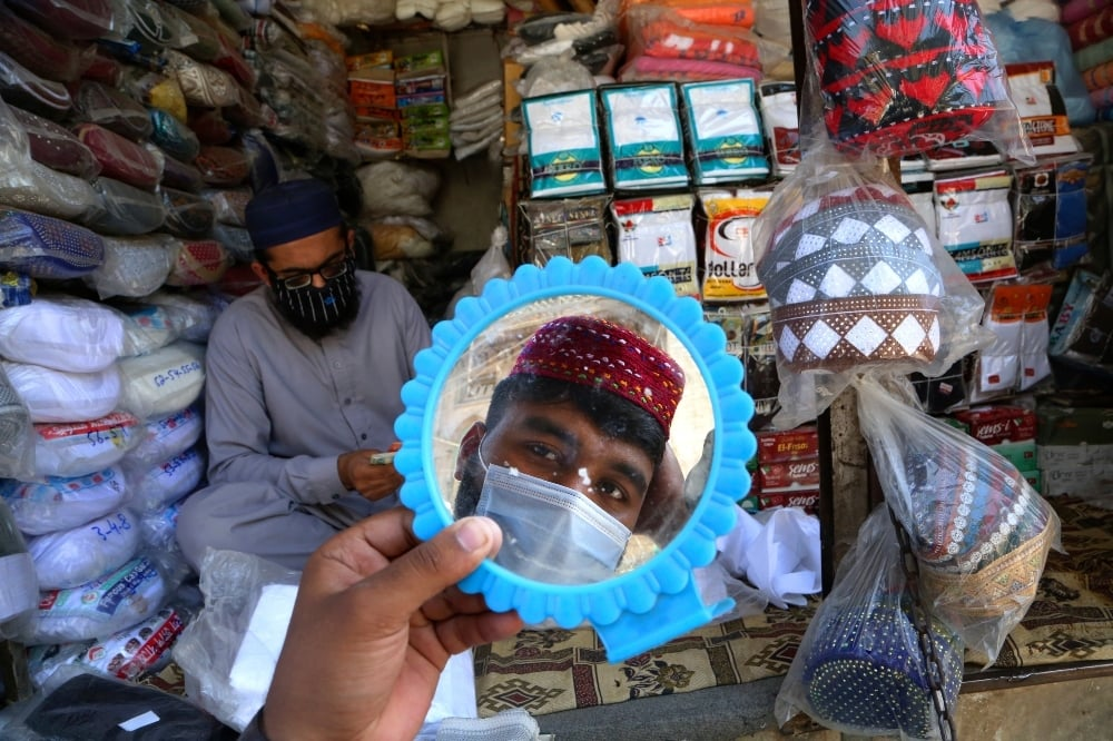 In this April 8 photo, a man tries on a traditional cap in preparation for the upcoming Muslim fasting month of Ramadan in Peshawar. — AP