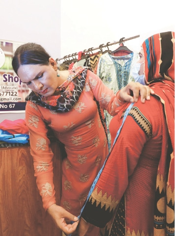 THIS April 5 photo shows Jiya taking the measurements of a customer at her shop in Karachi.—Reuters