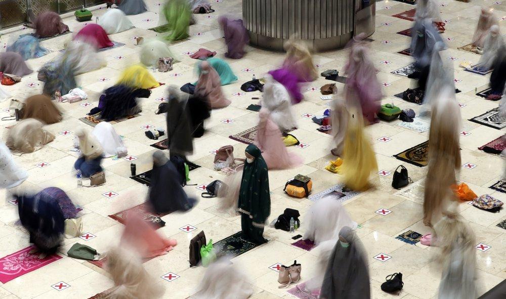In this photo taken using slow shutter speed, Muslim women offer Taraweeh. — AP
