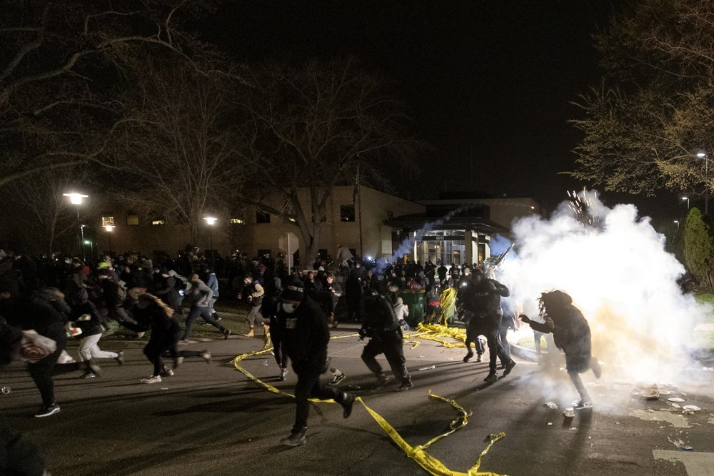 People run as police attempt to disperse the crowd at the Brooklyn Centre Police Department, late Sunday, in Brooklyn Centre. — AP