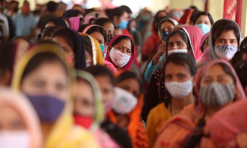Hindu devotees wearing face masks as a precautionary measure against the coronavirus wait to offer prayers inside a temple dedicated to goddess Kali in occupied Jammu, India, Tuesday, April 13. — AP