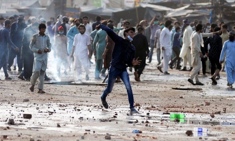 A supporter of Tehreek-i-Labaik Pakistan (TLP) hurls stones towards police (not in picture) during a protest against the arrest of their leader in Lahore, April 13. — Reuters