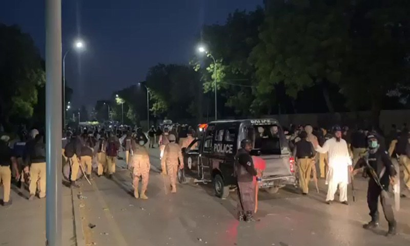 Police personnel and protesters seen at a protest site in Karachi on Tuesday evening. — DawnNewsTV