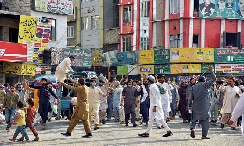 FAISALABAD: TLP activists carrying sticks force traders to shut shops at Ghanta Ghar Chowk. — Online