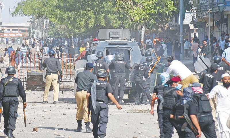 KARACHI: Policemen try to disperse protesters in Korangi on Tuesday.—Online