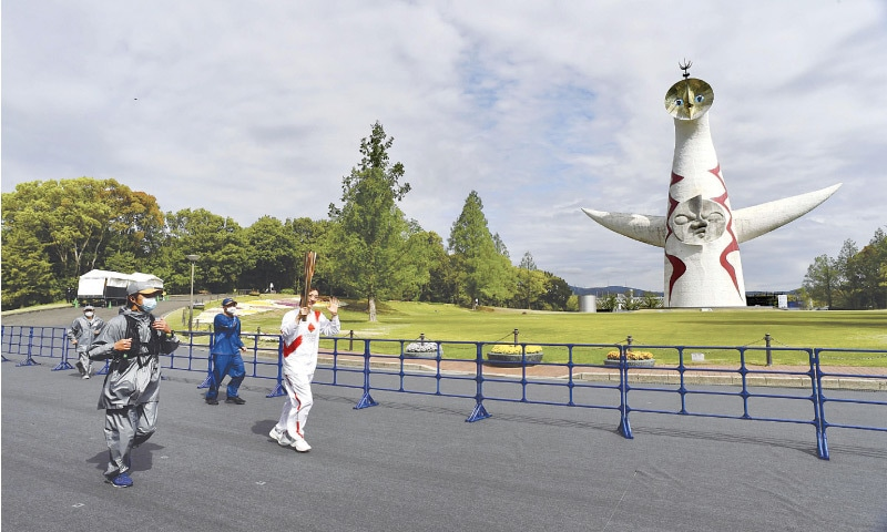 FORMER Japanese swimmer Aya Terakawa carries the Tokyo 2020 Olympic torch during the relay at the Expo '70 Commemorative Park in Suita on Tuesday.—AFP