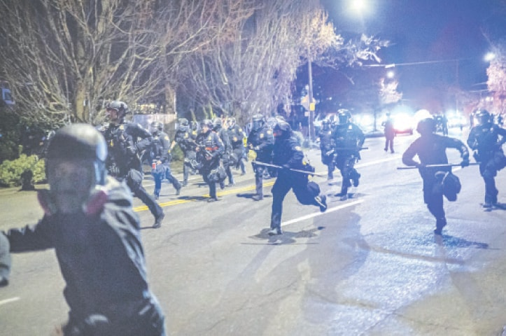 PORTLAND (Oregon): Police officers chase demonstrators during a protest against the killing of Daunte Wright.—AFP