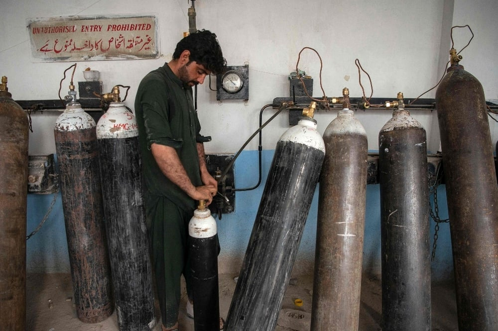 A worker fills oxygen cylinders for hospital use on Covid-19 coronavirus patients, at a factory in Peshawar on April 13. — AFP