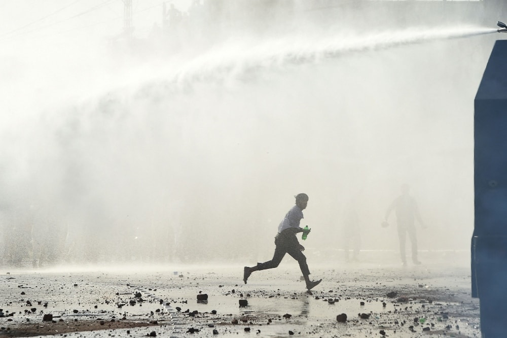 Police personnel use a water cannon to disperse TLP supporters during a protest in Lahore on April 13.  — AFP
