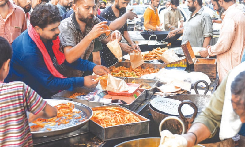Ignoring the advice of health experts, people line up for oily, fried iftar delights at Burnes Road on Wednesday.—Fahim Siddiqi/White Star