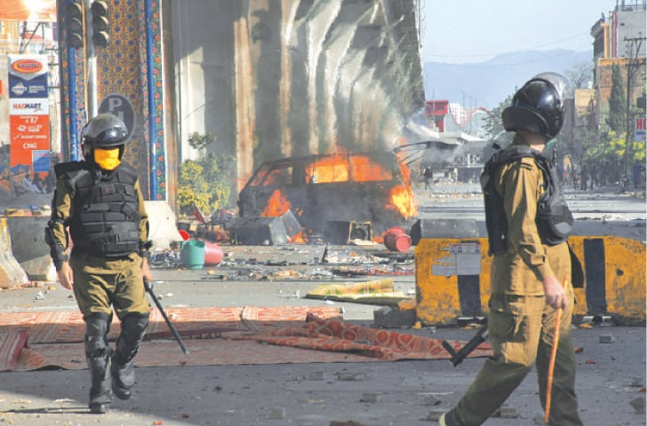 Policemen walk past a burning van torched by TLP protesters in Rawalpindi on Wednesday.—AP