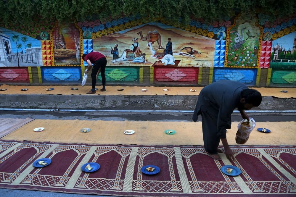 Volunteers arrange plates for people to use when breaking their fast in Peshawar on April 13. — AP