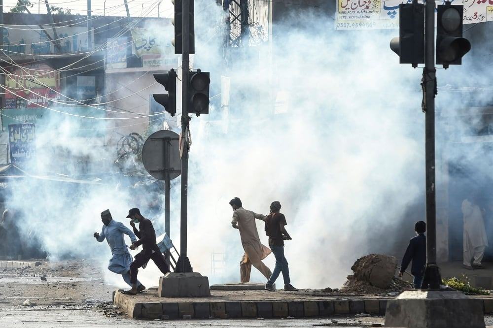 Supporters of the Tehreek-i-Labbaik Pakistan  disperse after police fired tear gas during a protest in Lahore on April 13. — AFP