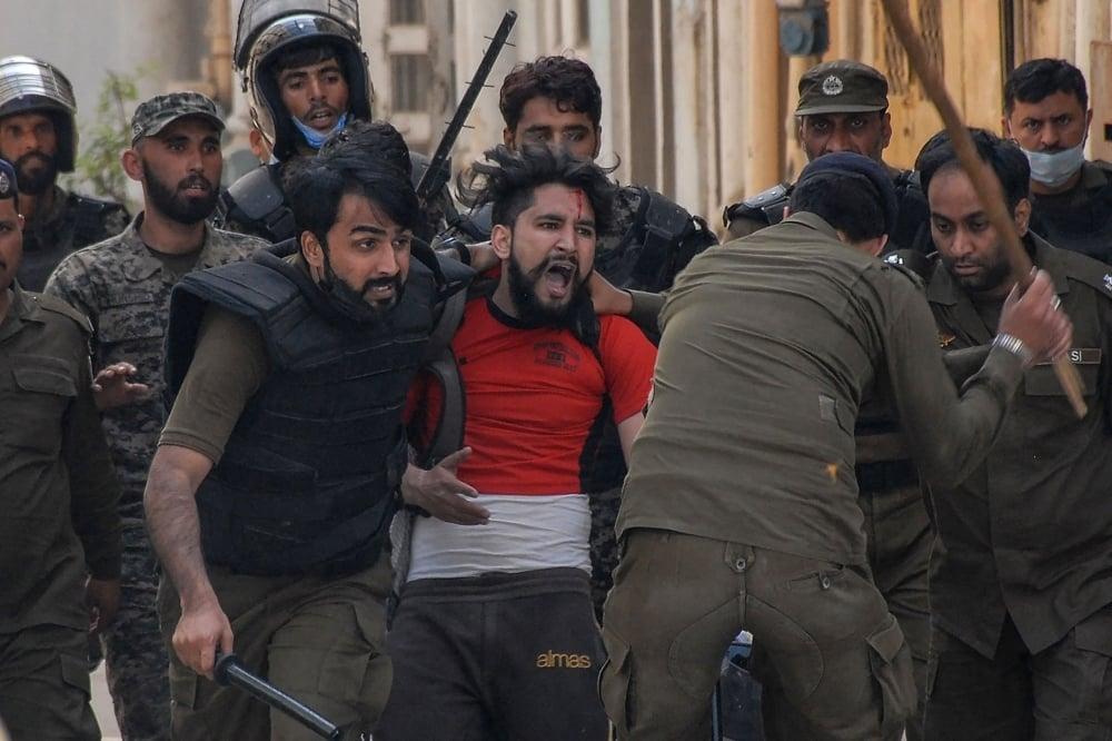Policemen detain a TLP supporter in Rawalpindi. — AFP