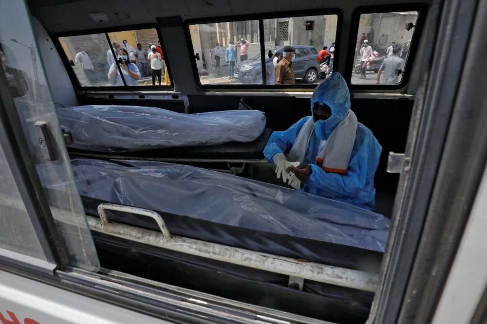 A man wearing a protective suit sits next to the bodies of the victims of the coronavirus disease inside an ambulance at a mortuary  of a hospital in Ahmedabad. — Reuters