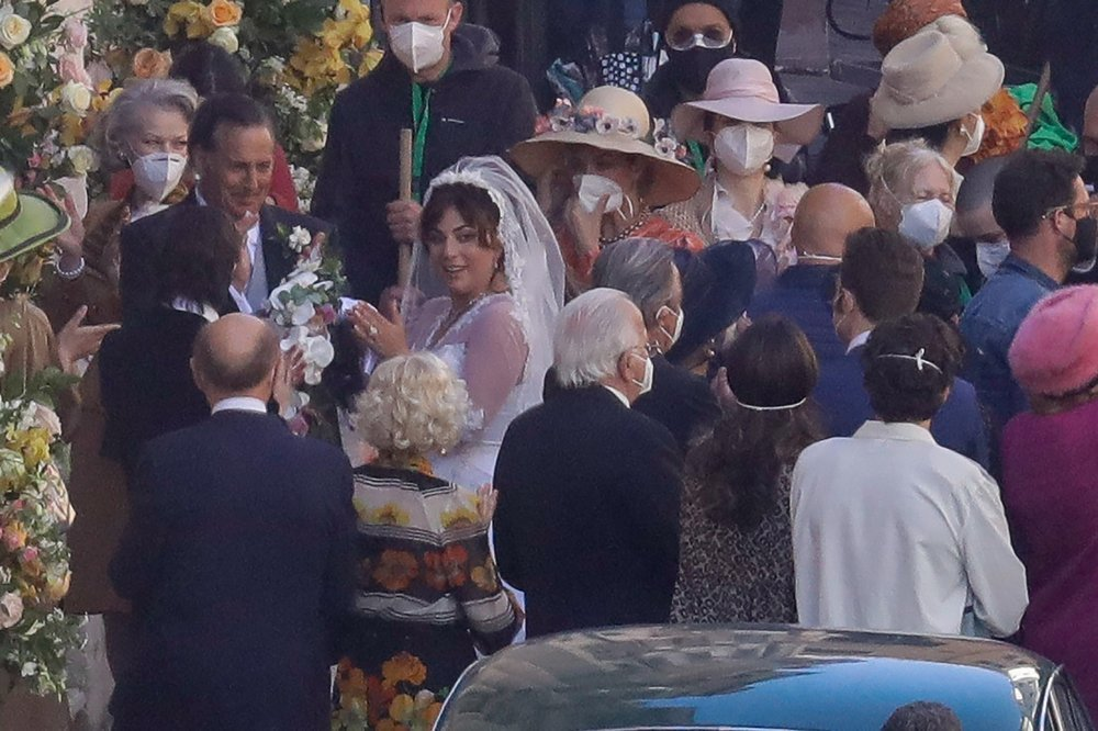 Lady Gaga, wearing a wedding dress in background left, plays Maurizio Gucci's former wife Patrizia Reggiani during the shooting of a movie by Ridley Scott. — AP