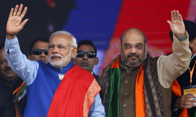 This file photo shows Indian Prime Minister Narendra Modi and Home Minister Amit Shah waving to their supporters during a campaign rally in New Delhi, India. — Reuters