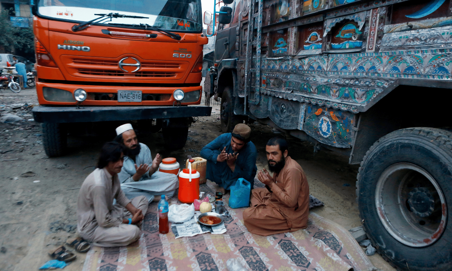 Truck drivers pray before breaking their fast in Lahore on Thursday. — AP