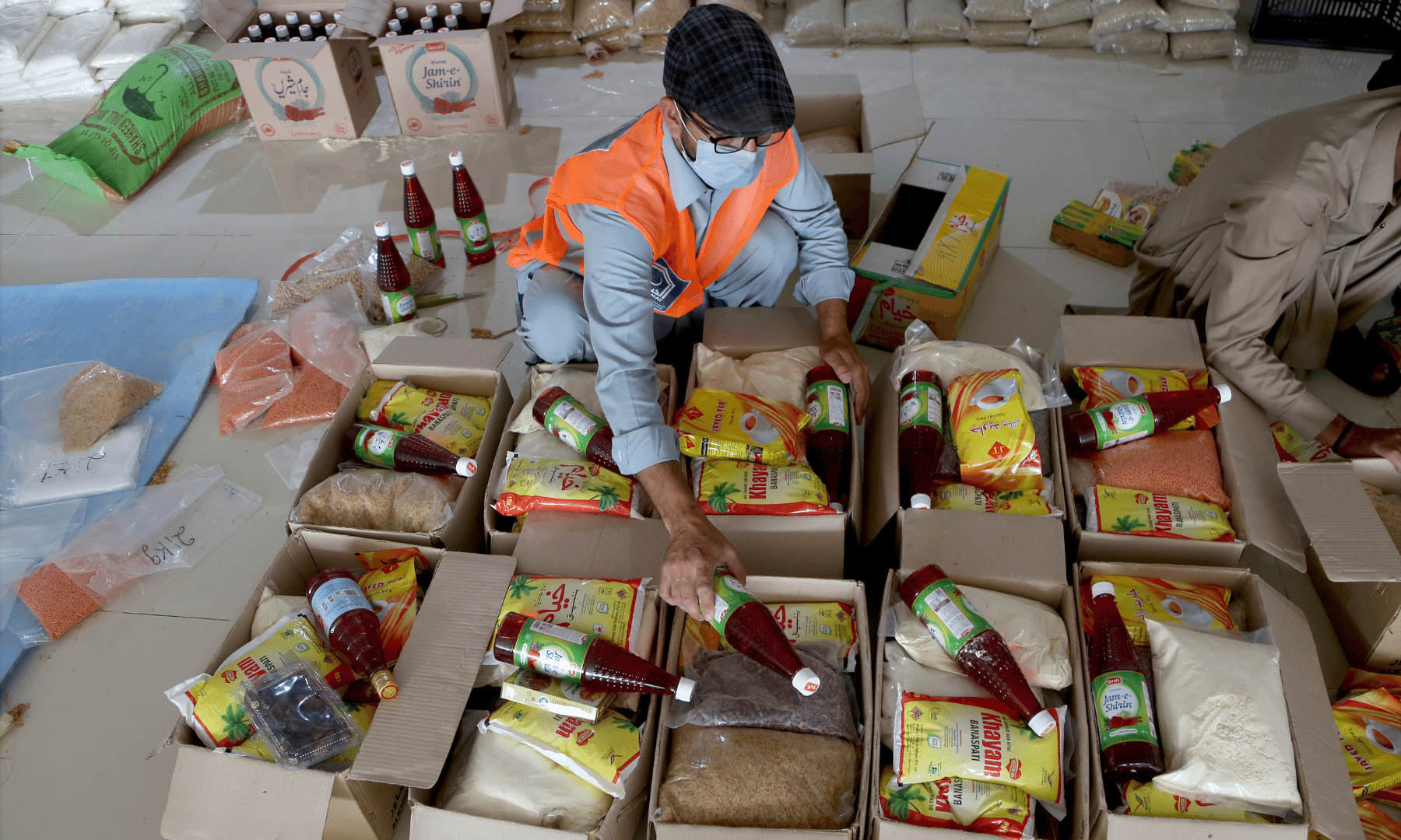 Workers from 'Alkhidmat Foundation Pakistan' prepare boxes of food and groceries to be distributed for free among needy people during Ramazan, in Peshawar. — AP