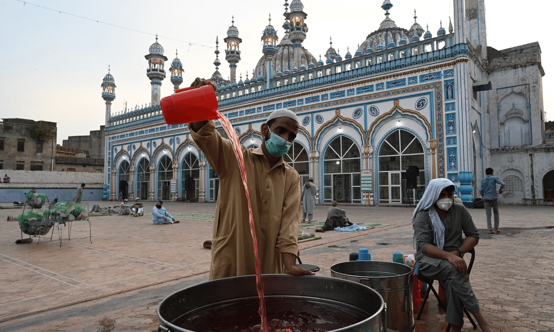 A volunteer prepares drinks for worshippers before they break their fast on the first day of Ramazan, at the Jamia Mosque in Rawalpindi on Wednesday. — AFP