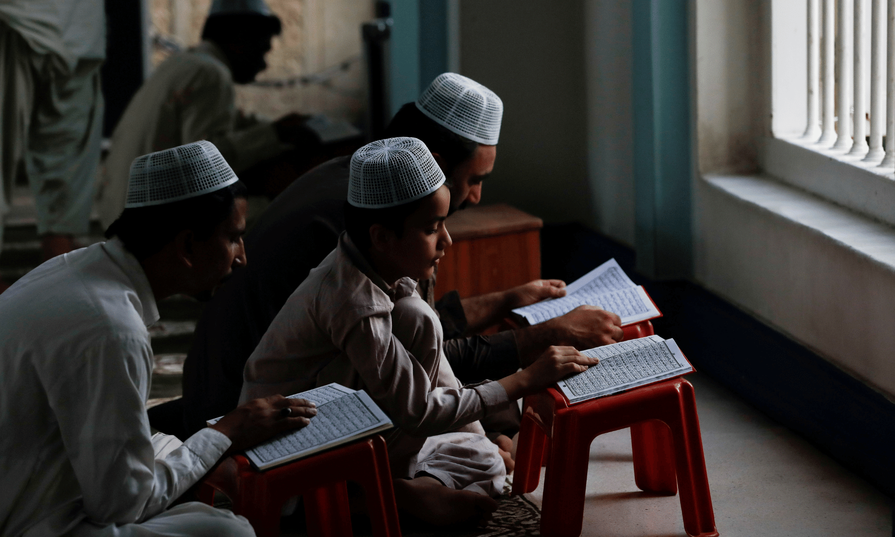 People read the Holy Quran during Ramazan, as the outbreak of the coronavirus disease continues, at a mosque in Karachi. — Reuters