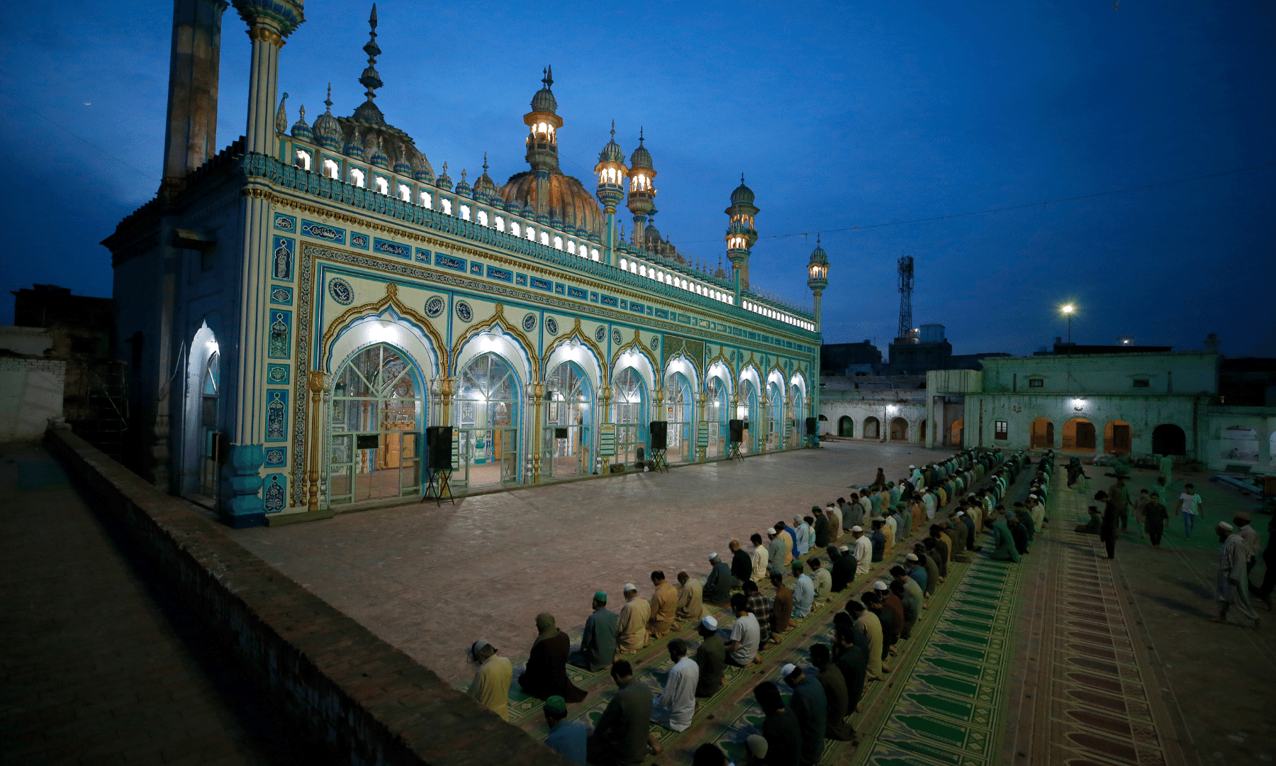 Worshippers perform evening prayers after breaking their fast in Rawalpindi. — AP