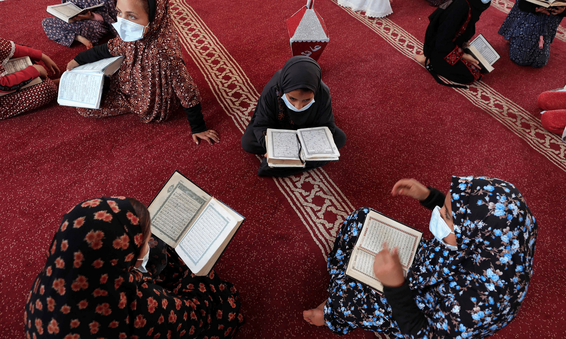 Young Palestinian girls wearing face masks due to the coronavirus pandemic, read the Quran during Ramazan, in Gaza City. — AFP