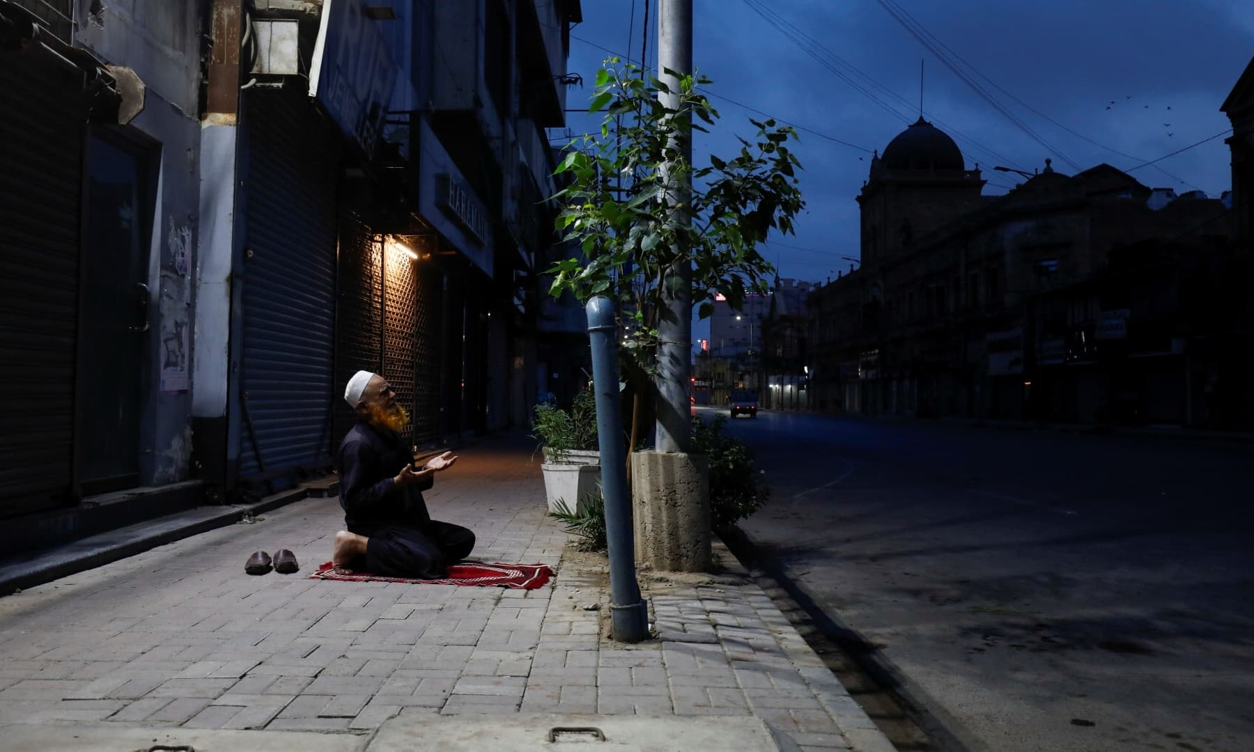 Mohammad Said, 65, a private security guard, offers an evening prayer after Iftar along a sidewalk in front of closed shops in Karachi, April 15. — Reuters