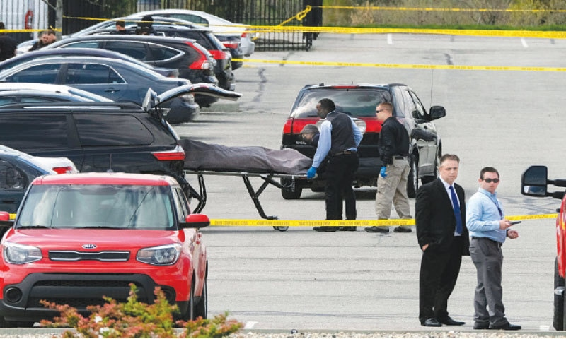 INDIANAPOLIS: Officials load a body into a vehicle on Friday at the site of the mass shooting. — AFP