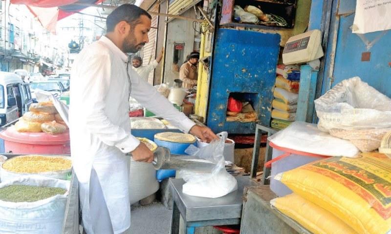 A shopkeeper weighs sugar at his shop in Rawalpindi's Ganjmandi area. — Photo by Mohammad Asim/File