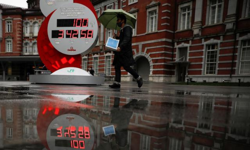 A countdown clock showing that 100 days are left until Tokyo 2020 Olympic Games that have been postponed to 2021 due to the coronavirus  pandemic is reflected in a puddle in Tokyo, Japan. — Reuters/File