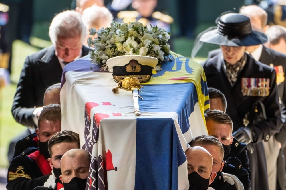 Pall Bearers carry the coffin of Britain's Prince Philip, Duke of Edinburgh, followed by members of the Royal family inside St George's Chapel in Windsor Castle on April 17. — AFP