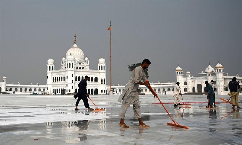Workers clean the floor at the Shrine of Baba Guru Nanak Dev at the Gurdwara Darbar Sahib, ahead of its opening in Kartarpur. — AFP/File