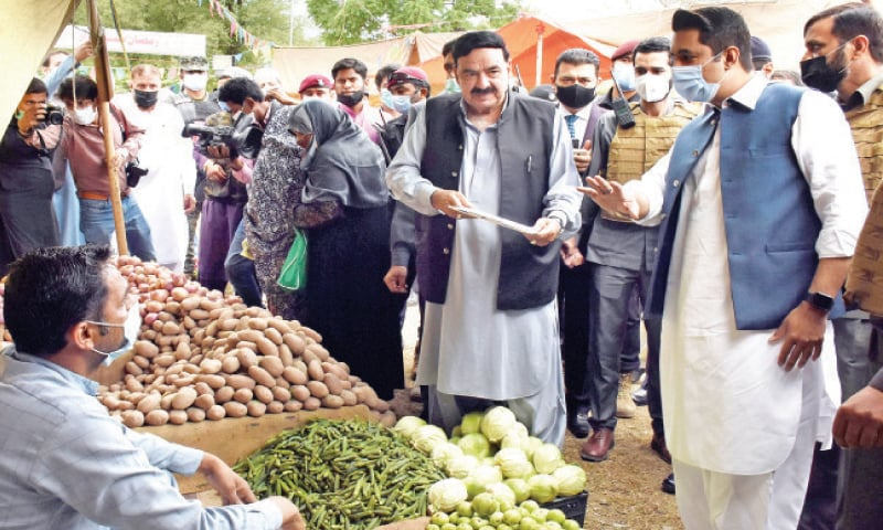Interior Minister Sheikh Rashid Ahmed being briefed on the rate list during his visit to a Sasta bazaar in G-7 on Sunday. — Online