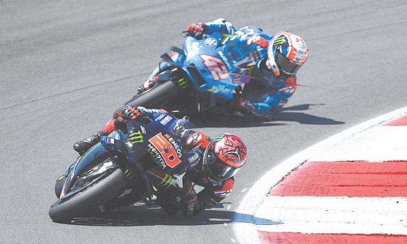 Yamaha's Fabio Quartararo and Suzuki's Alex Rins (back) compete during the Portuguese MotoGP on Sunday.—AFP