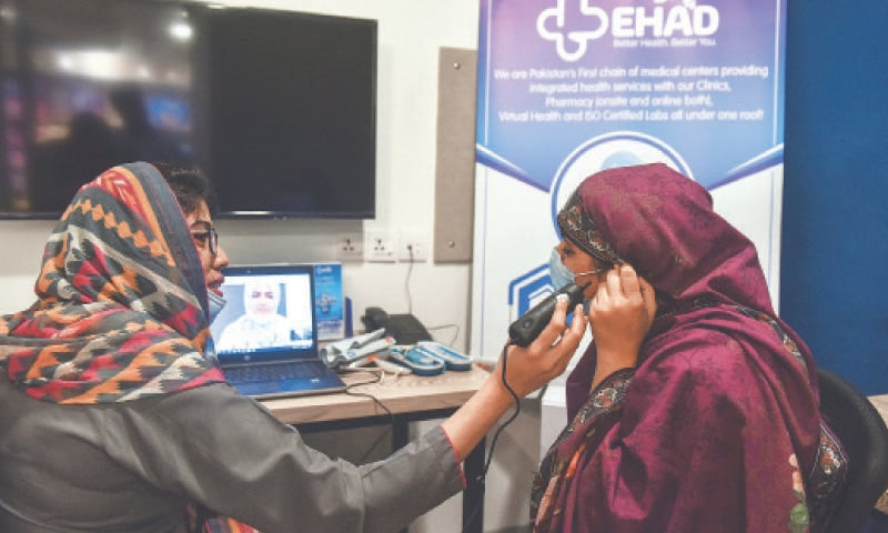 WITH a specialist available over video link, a patient [right] is being assisted by a paramedic for tele-consultation using digital health gadgets at a telehealth centre in Karachi.—Fahim Siddiqi / White Star