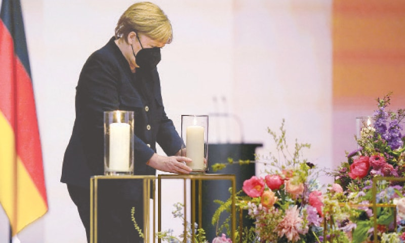 GERMAN Chancellor Angela Merkel places a candle during the ceremony for coronavirus victims.—AFP