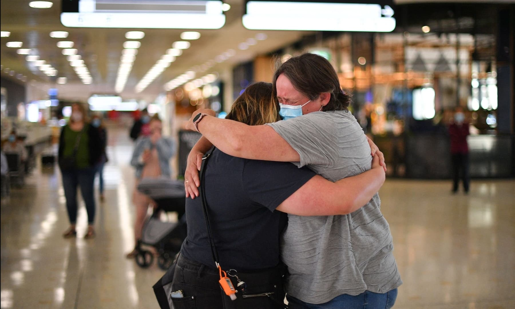 A mother (R) embraces her daughter upon her arrival from New Zealand at Sydney International Airport on April 19. — AFP